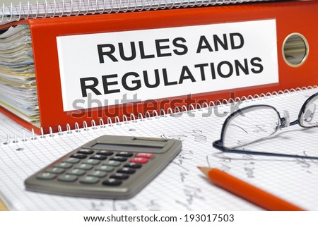 rules and regulations written on folder - stock photo