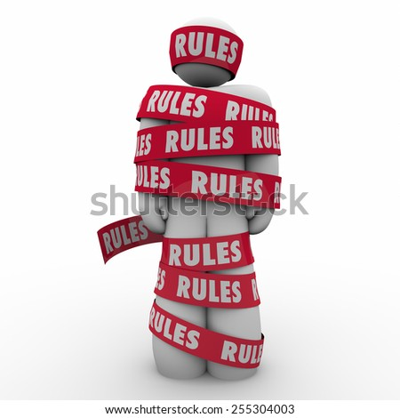 Rules word on red tape wrapped around a man or person to illustrate following regulations, guidance or laws to be in compliance  - stock photo