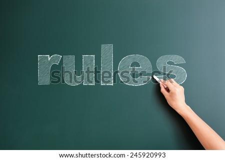 rules written on blackboard - stock photo