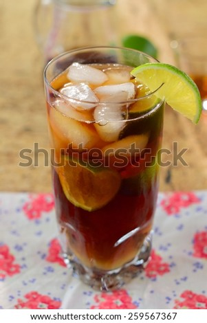 Rum and Coke Cocktail Drink with Lime Wedges on The Rocks - stock photo
