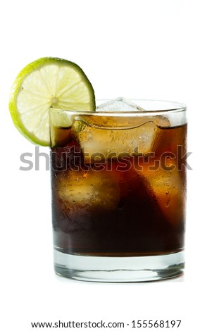 rum and cola with a lime garnish isolated on a white background - stock photo