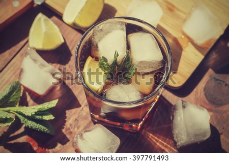 rum cocktail in a glass with ice, lime, mint, bread on a wooden table, brandy - stock photo