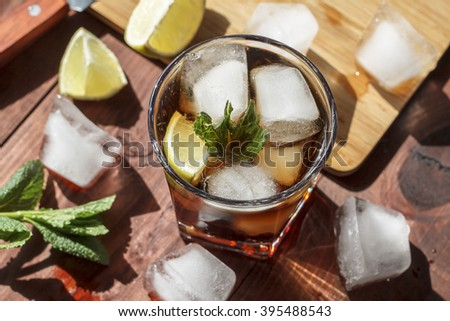 rum cocktail in a glass with ice, lime, mint, bread on a wooden table,  brandy, cuba Libre - stock photo
