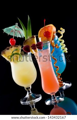 Rum Runner, Bahama Mama, and Blue Lagoon cocktaisl over black background on reflection surface, garnished with pineapple flag, fresh raspberry, maraschino cherry, and lime twist.  - stock photo