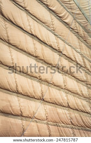 Rumpled sewed-in sail of light brown color. Vietnamese boat sail in close up view. Abstract backgrounds and wallpapers. Materials, textiles and fabric texture. - stock photo