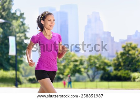 Run woman exercising in Central Park New York City with urban background of skyscrapers skyline. Active Asian female runner running with purple t-shirt and shorts sportswear. - stock photo