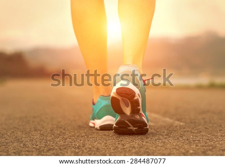Runner athlete feet running on road under sunlight. - stock photo