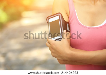 Runner athlete listening to music from smart phone mp3 player smart phone armband.woman fitness jogging workout wellness concept.  - stock photo