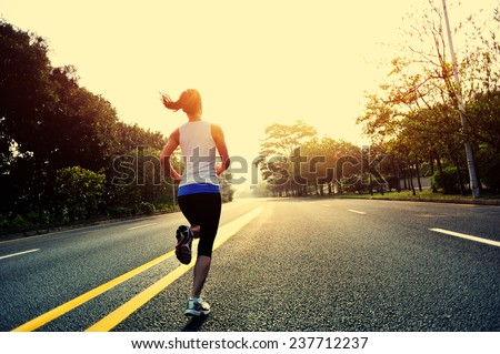 Runner athlete running at road. - stock photo