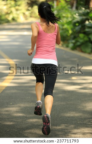 Runner athlete running at road. woman fitness jogging workout wellness concept.  - stock photo