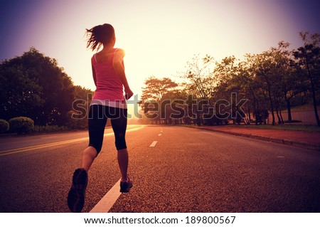 Runner athlete running at road. woman fitness sunrise jogging workout wellness concept.  - stock photo