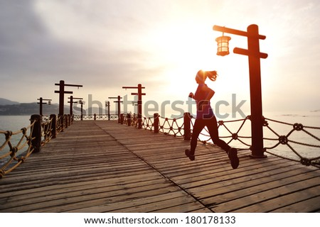 Runner athlete running at seaside wooden pier. woman fitness silhouette sunrise jogging  workout wellness concept.  - stock photo