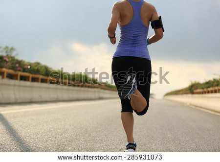 Runner athlete running on road. woman fitness jogging workout wellness concept.  - stock photo