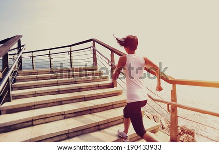 Runner athlete running on seaside stone stairs. woman fitness jogging workout wellness concept.  - stock photo