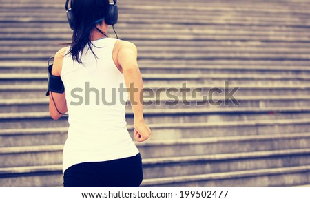Runner athlete running on stairs. listening to music in headphones from smart phone mp3 player smart phone armband.woman fitness jogging workout wellness concept.  - stock photo