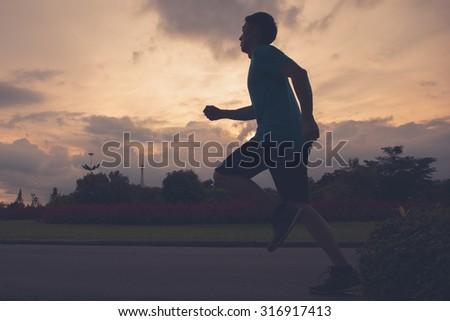 Runner athlete silhouette running in public park. man fitness sunrise jogging workout wellness concept. - stock photo