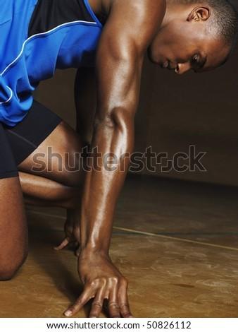 Runner crouching down, side view - stock photo
