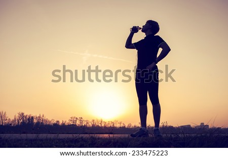 Runner drinks water after training - stock photo