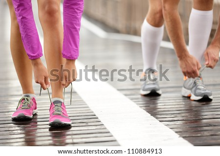 Runner feet. Running couple closeup of running shoes. Woman barefoot running shoes in foreground. Couple jogging on Brooklyn Bridge, New York. - stock photo