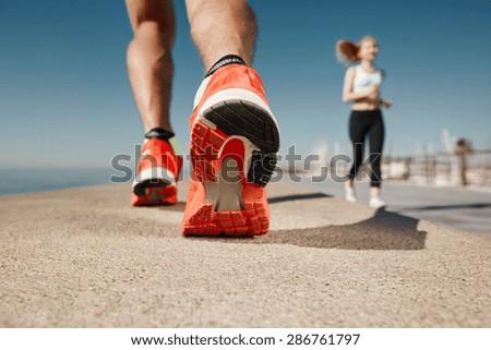 Runner feet running on road closeup on shoe. Sportsman fitness sunrise jog workout welness concept. - stock photo