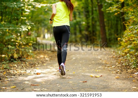 Runner feet running on road closeup on shoes in park - stock photo