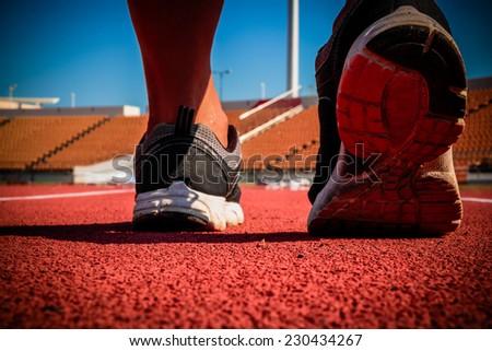 Runner feet running on running track - stock photo