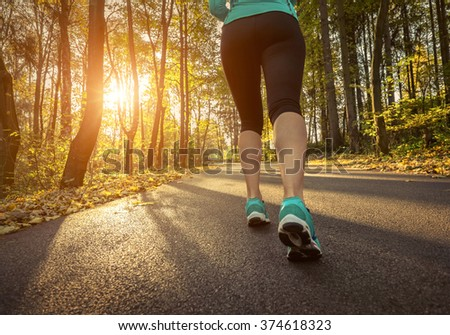 Runner in action at autumn. - stock photo