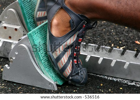 runner in blocks at track meet - stock photo