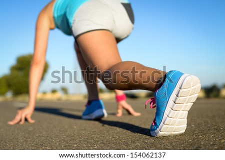 Runner in starting line ready for running and sprint. Sport footwear detail. Female athlete with blue sport shoes training in road. - stock photo