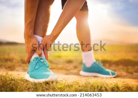 Runner leg and muscle pain during running training outdoors in summer nature - stock photo