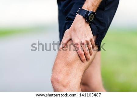 Runner leg and muscle pain during running training outdoors in summer nature. Health and fitness concept. Injured male jogger massage sore leg. - stock photo
