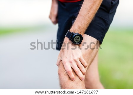 Runner leg and muscle pain during running training outdoors in summer nature, sport jogging physical injury, workout. Health and fitness concept - stock photo