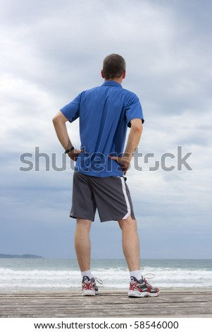 Runner making a break at the sea - stock photo