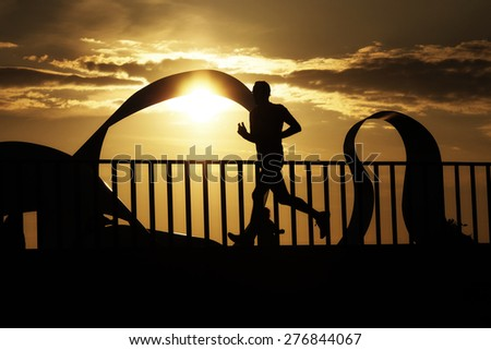 runner man athlete silhouette  in the seafront promenade city  at sunset in Corunna Spain - stock photo