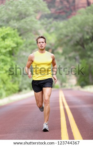 Runner man running with concentration, determination and strength in full length on road. Fit male sport fitness model sprinting outdoors. - stock photo