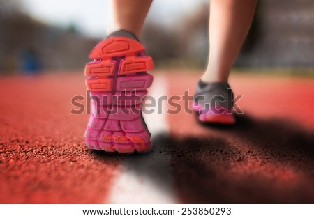 runner on a track with a close up of the shoes mid-stride on the pavement with an drama filter (shallow depth of field) - stock photo