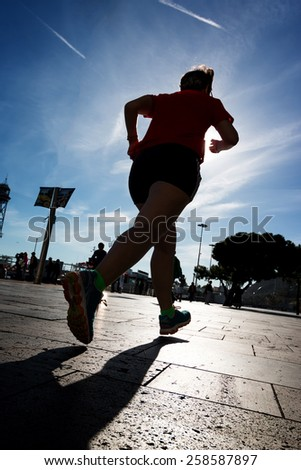 Runner on the street in the town - stock photo
