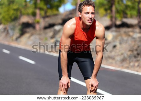 Runner resting after running. Jogging man taking a break during training outdoors in on mountain road. Young Caucasian male fitness model after work out. - stock photo