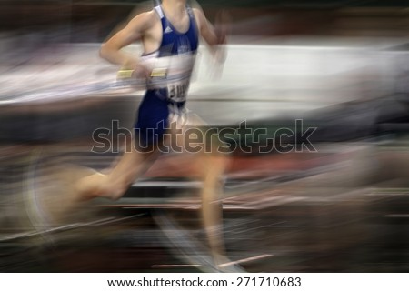 Runner running a race around a track with  lines holding baton relay - stock photo