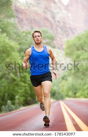 Runner - running athlete man. Male sprinting during outdoors training for marathon run. Athletic fit young sport fitness model in his twenties in full body length on road outside in nature. - stock photo