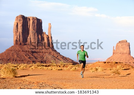 Runner. Running man sprinting in Monument Valley. Athlete runner cross country trail running outdoors in amazing nature landscape. Fit male sports model in fast sprint at speed, Arizona Utah, USA. - stock photo