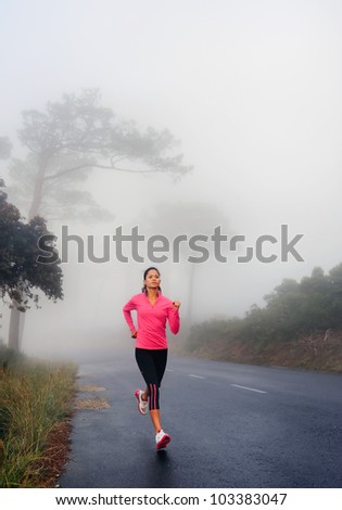 runner running outdoor fitness healthy lifestyle woman workout. female jogger on road run through misty forest early in the morning. - stock photo