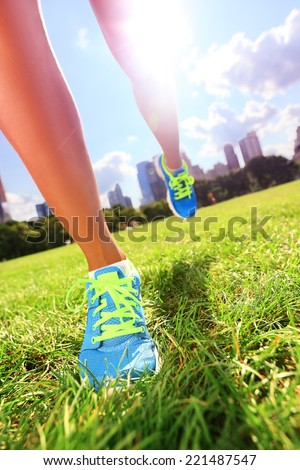 Runner - running shoes closeup of woman athlete running shoes on grass. Female jogger womens shoes in Central Park, New York City. - stock photo