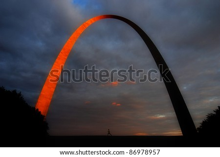 Runner running under the glowing St. Louis Arch at sunset - stock photo