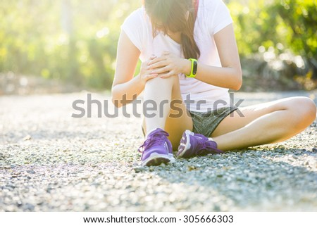 Runner sport knee injury. Woman in pain while running in park - stock photo