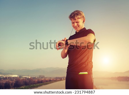 Runner starts his modern stopwatch before jogging - stock photo
