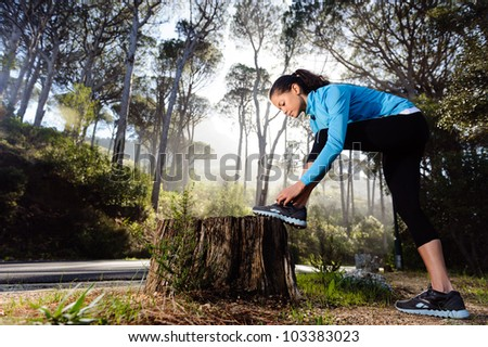 runner tying her shoelace while preparing for fitness training outdoors in the forest with morning sunlight - stock photo