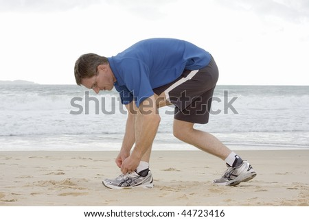 Runner tying his shoes on a beach - stock photo