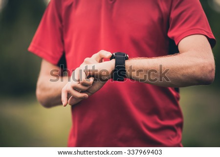 Runner using heart rate monitor training running, smartwatch checking performance or GPS. Man athlete looking at stopwatch. Healthy runner closeup when working out. Technology for tracking activity. - stock photo