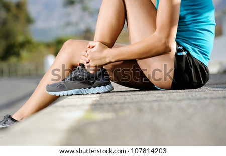 runner with ankle injury holds foot to reduce pain. running problem for athlete training outdoors - stock photo